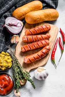 自家製ホットドッグを作るための材料。ソーセージ、焼きたてのパン、マスタード、ケチャップ、キュウリ。白色の背景。上面図