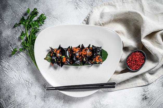 黒点心餃子。アジア料理。灰色の背景。上面図