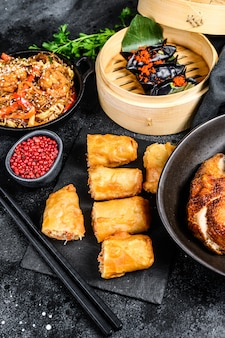 中華料理セット、食品黒背景。中華麺、餃子、北京ダック、点心、春巻き。有名です。上面図
