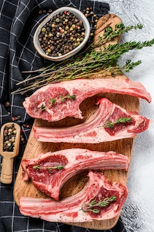 コショウとタイムの生の新鮮な子羊のリブ。有機肉。白色の背景。上面図