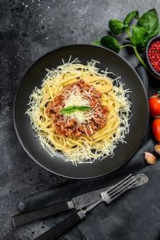 トマトソース、チーズパルメザンチーズ、バジルのイタリアンスパゲッティパスタ。黒の背景。上面図
