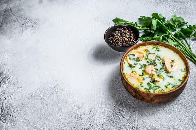 サーモン、マス、ジャガイモ、パセリのクリーミーな魚のスープ。灰色の背景、上面図、テキスト用のスペース