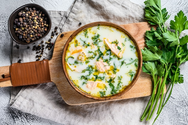 サーモン、マス、ジャガイモ、パセリのクリーミーな魚のスープ。灰色の背景、トップビュー。