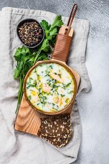 サーモンとジャガイモのフィンランドのクリーミーな魚のスープ。灰色の背景、トップビュー。