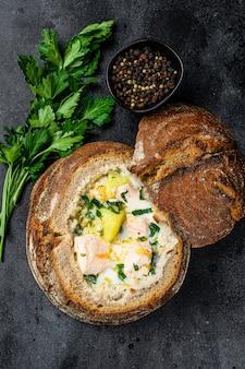 サーモンのスープをパンで提供しています。クリーミーなボリュームのある魚のスープ。健康とダイエット食品のコンセプト。黒の背景、トップビュー。