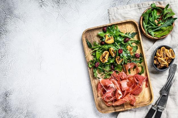 Салат с пармой, ветчиной прошутто, рукколой и инжиром. итальянские закуски. серый фон, вид сверху, место для текста