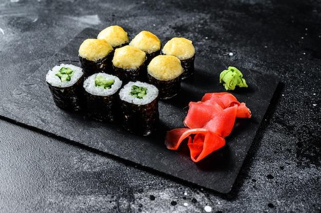 さまざまな種類の寿司が黒い石の上で提供されます。黒の背景。上面図
