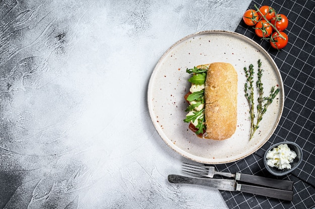 Сэндвич чиабатта со свежим козьим сыром, грушевым мармеладом и рукколой. серый фон вид сверху. пространство для текста
