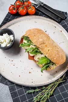 新鮮なカマンベールチーズ、ナシマーマレード、リコッタチーズ、ルッコラのサンドイッチ。灰色の背景。上面図