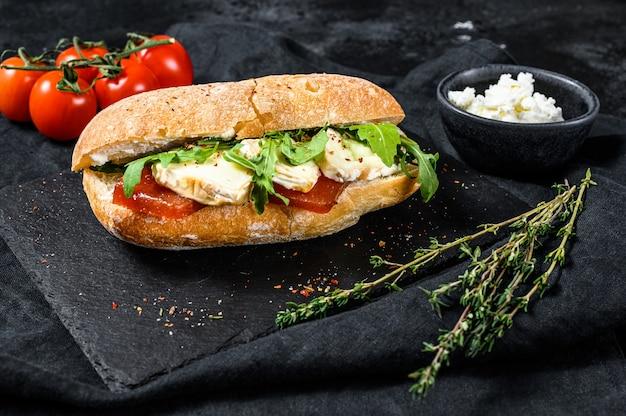 新鮮なカマンベールチーズ、ナシマーマレード、リコッタチーズ、ルッコラのサンドイッチ。黒の背景。上面図