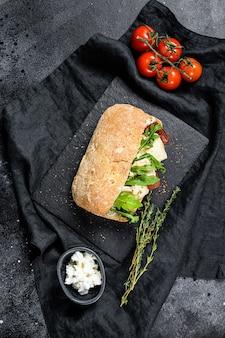 Сэндвич чиабатта со свежим козьим сыром, грушевым мармеладом и рукколой. черный фон. вид сверху