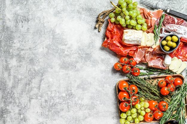 ぶどう、生ハム、スライスハム、ビーフジャーキー、チョリソサラミ、フエット、カマンベール、ヤギのチーズの冷製前菜盛り合わせ。灰色の背景。上面図。コピースペース