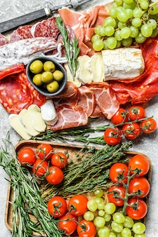 前菜セット盛り合わせ。ソーセージ、スライスしたハム、生ハム、ベーコン、オリーブの冷製スモーク肉プレート。前菜各種。灰色の背景。上面図