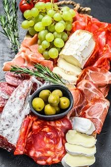 ぶどう、生ハム、スライスハム、ビーフジャーキー、チョリソサラミ、フエット、カマンベール、ヤギのチーズの冷製前菜盛り合わせ。黒の背景。上面図