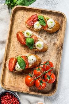トマト、モッツァレラチーズ、バジルのブルスケッタ。イタリアの前菜やスナック、前菜。灰色の背景。上面図