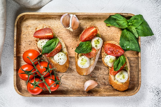 トマト、モッツァレラチーズ、バジルのサンドイッチ。イタリアの前菜、前菜。灰色の背景。上面図