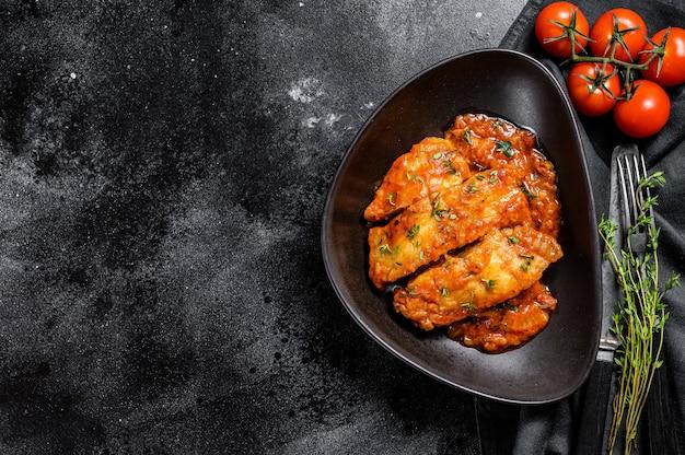 オヒョウの魚のトマトソース焼き。黒の背景。上面図。コピースペース