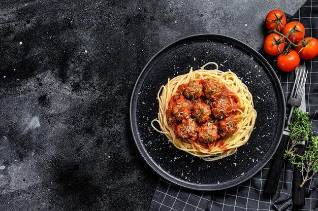 Итальянская паста спагетти с томатным соусом и фрикадельками. черный фон. вид сверху. копировать пространство