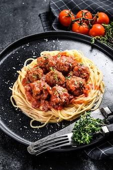 Итальянская паста спагетти с томатным соусом и фрикадельками. черный фон. вид сверху