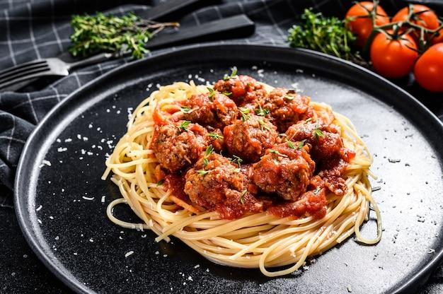 Макароны спагетти с фрикадельками и томатным соусом. итальянская кухня. черный фон. вид сверху