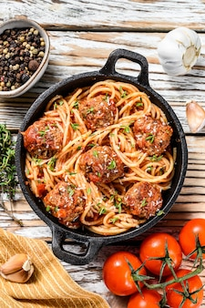 Итальянские макароны спагетти с томатным соусом и фрикадельками в чугунной сковороде с сыром пармезан. белый деревянный фон. вид сверху