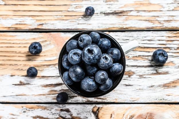 Черника в белой чашке. антиоксидант органический суперпродукт. концепция для здорового питания. белый фон. вид сверху