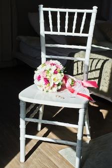 Букет невесты и золотые обручальные кольца на стуле.