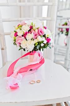 Свадебный букет из белых и розовых роз и коал на стуле.