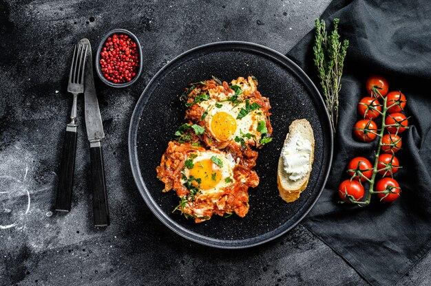 Шакшука в темной тарелке со свежими ингредиентами