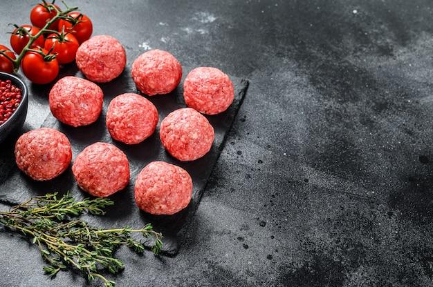 生のミートボール、豚挽肉。黒の背景。上面図。コピースペース
