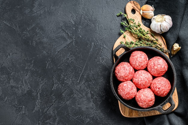 Рецепт приготовления фрикадельок из говяжьего фарша на сковороде. черный фон. вид сверху. копировать пространство