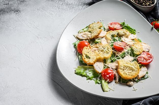 Салат цезарь с курицей гриль, гренками, перепелиными яйцами и помидорами черри. белый фон.