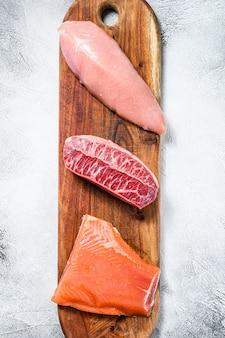 まな板の上の生の肉の種類。ビーフトップブレード、サーモンフィレ、七面鳥の胸肉。白のステーキ。上面図。コピースペース