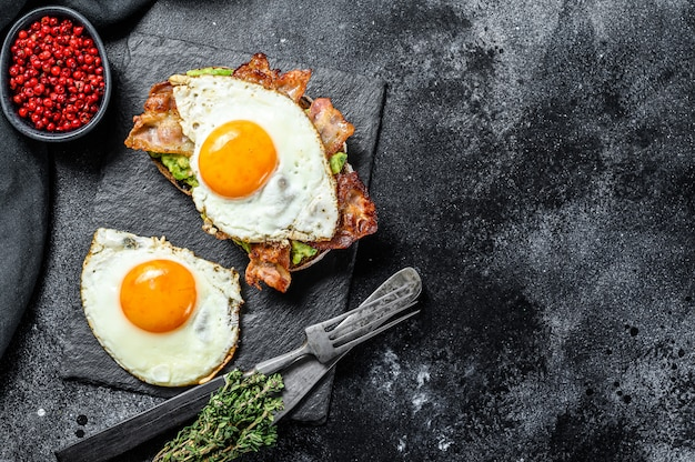 Открытый бутерброд с авокадо, жареным беконом и яйцом на черном. вид сверху. копировать пространство