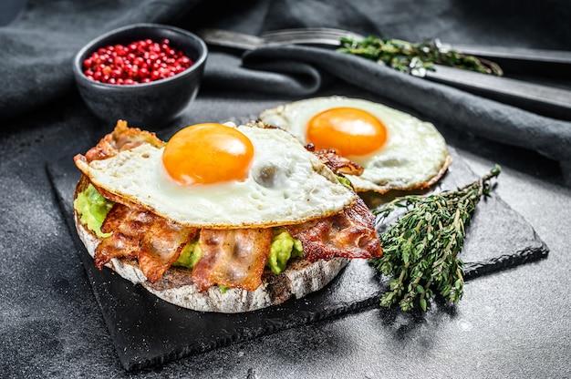Открытый бутерброд с авокадо, жареным беконом и яйцом на черном. вид сверху.