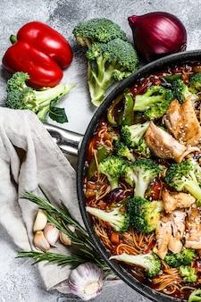 野菜と肉を調理鍋にアジアの卵麺。灰色の壁。上面図