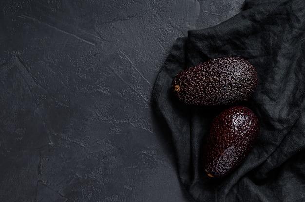 Коричневый спелый авокадо. черная стена. вид сверху. пространство для текста