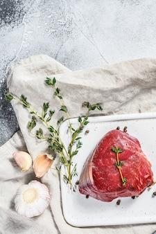 マーブルビーフのテンダーロイン。白いまな板に生のフィレミニョンステーキ。灰色の壁。上面図