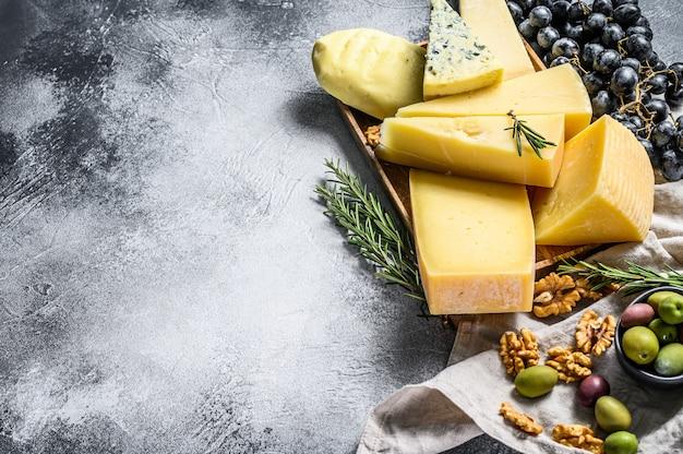 Сырная тарелка подается с виноградом, крекерами, оливками и орехами. ассорти вкусных закусок. серая стена. вид сверху. пространство для текста