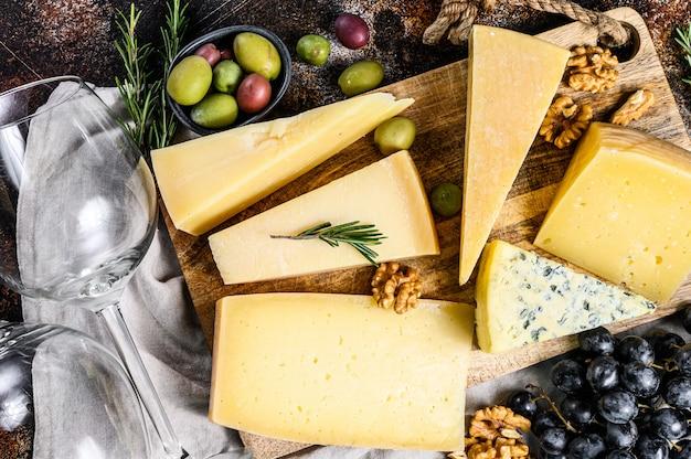Коллекция швейцарских, голландских, французских, итальянских сыров с орехами и виноградом. темная стена. вид сверху