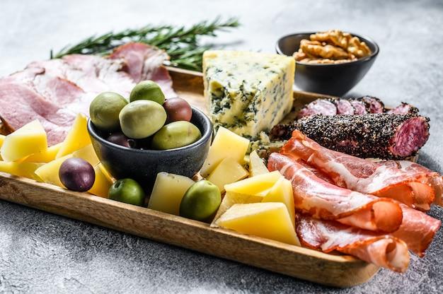 前菜各種前菜、生ハム、サラミ、コッパ、チーズ、オリーブのまな板。灰色の壁。上面図