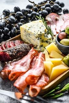 Антипасто различные закуски, разделочная доска с прошутто, салями, коппа, сыр и оливки. серая стена. вид сверху