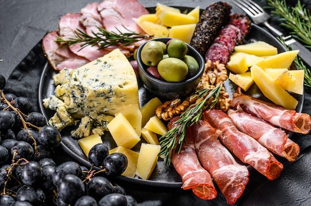 スライスした肉、ハム、サラミ、チーズ、オリーブの前菜ボード。黒い壁。上面図