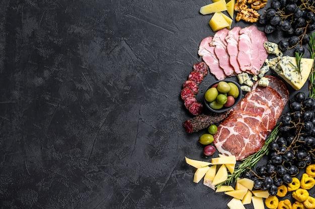 典型的なイタリアの前菜、生ハム、ハム、チーズ、オリーブ。黒い壁。上面図。テキストのためのスペース