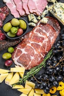 典型的なイタリアの前菜、生ハム、ハム、チーズ、オリーブ。黒い壁。上面図