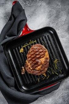 ローズマリーとニンニクを鍋に焼きリブアイステーキ。霜降りアイベ肉。上面図