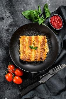 Итальянская домашняя паста каннеллони с говядиной и томатным соусом. вид сверху