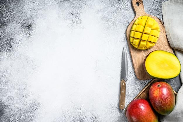 Спелые нарезанные фрукты манго на разделочную доску. вид сверху. копировать пространство
