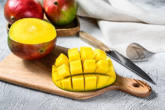 Плоды манго нарезать кубиками на разделочную доску. вид сверху