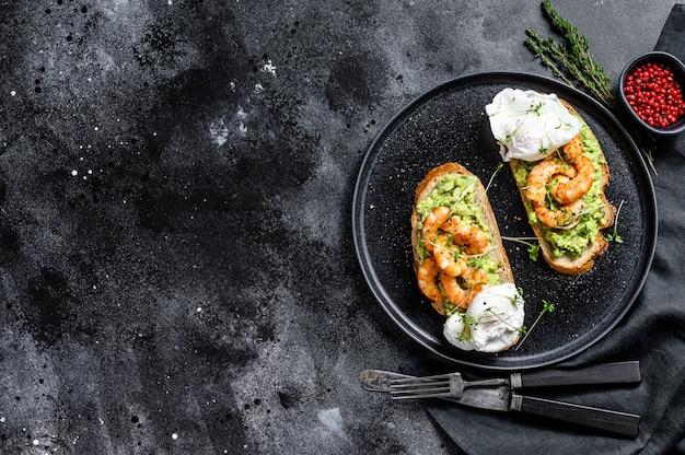 Бутерброд со свежими креветками, креветками на авокадо с яйцом. здоровая еда, скандинавская кухня. вид сверху. копировать пространство